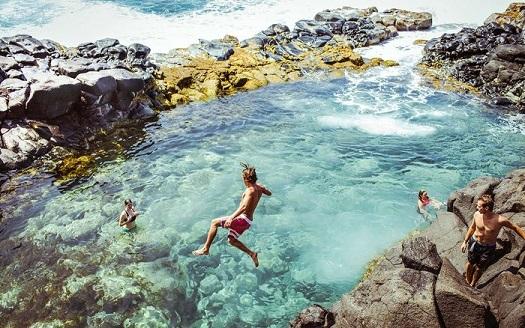 Friends having fun in Queen's Bath, Kauai, Kauai County, Hawaii, USA