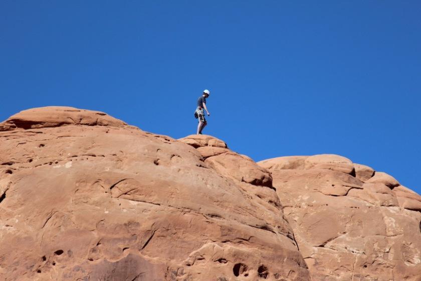 A climber on the rock beside the Balanced Rock